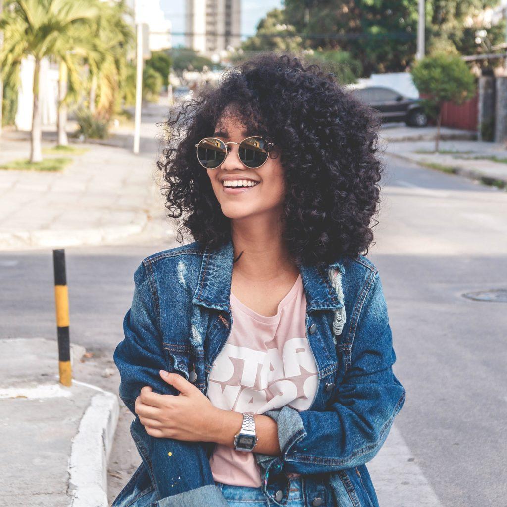 women's wearing blue denim jacket standing on the street